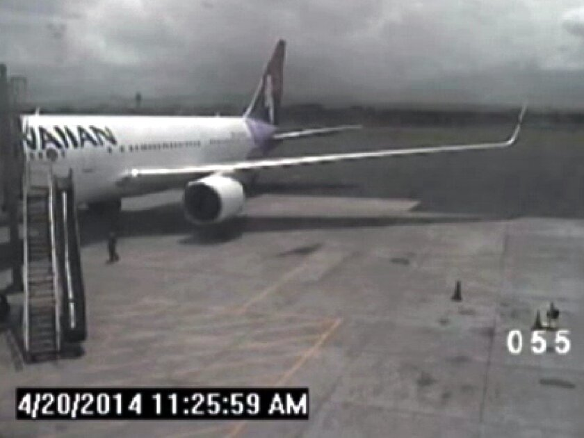 FILE - In this April 20, 2014, file image taken from a surveillance video provided by the Hawaii Department of Transportation, shows a California teen, left, after hopping from a jet's wheel well in Maui, Hawaii. When it was time for that same jet to leave, the pilot, who was a different pilot than the one who had landed the jet there, said security and mechanics were holding him up, according to a ten minute Federal Aviation Administration audio recording, provided exclusively to The Associated Press in response to a Freedom of Information Act request. (AP Photo/Hawaii Department of Transportation, File)