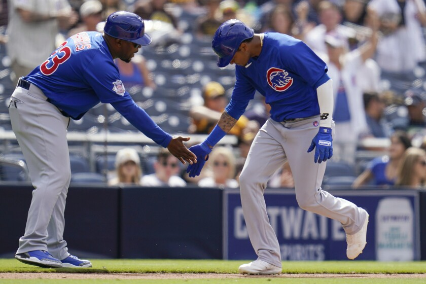 Chicago Cubs' Sergio Alcantara, right, is congratulated by third base coach Willie Harris after hitting a home run during the eighth inning of the team's baseball game against the San Diego Padres, Wednesday, June 9, 2021, in San Diego. (AP Photo/Gregory Bull)
