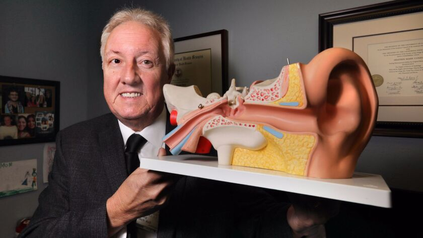 Portrait of North County audiologist David Illich holding a large model of the human ear in his Escondido office.