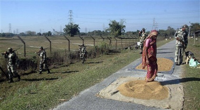 A woman lays out rice grains to dry as Border Security Force soldiers patrol near the India-Bangladesh border in Fulbari, about 25 kilometers (16 miles) from Siliguri, India, Thursday, Dec. 9, 2010. India's security forces routinely gun down cattle smugglers and other civilians crossing the border