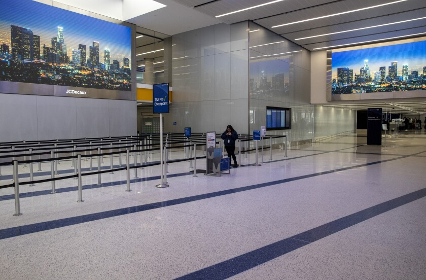An airport worker stands in a nearly empty TSA Pre lineup at Terminal 7 at Los Angeles International Airport on Saturday.