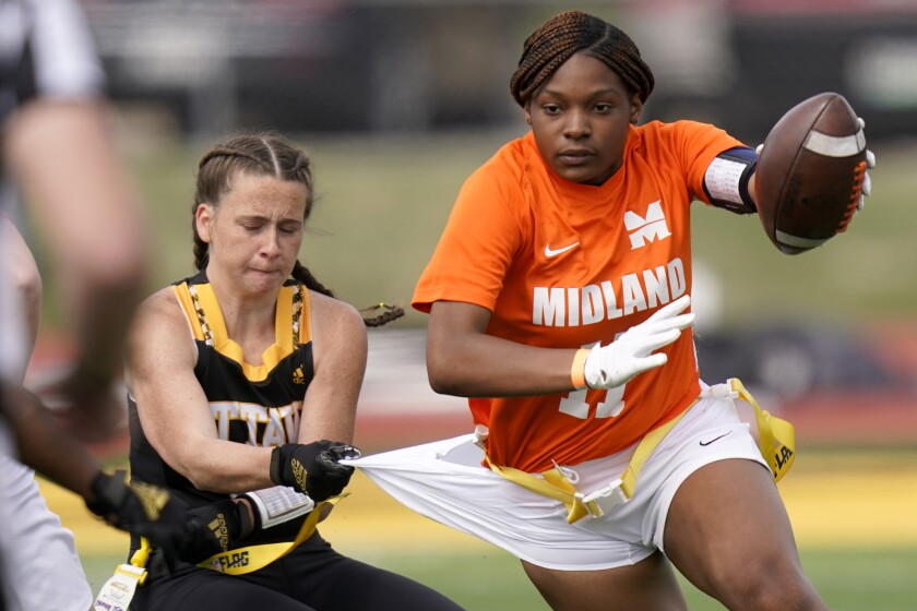 Ottawa defensive end Jennifer Anthony, left, tackles Midland's JaNasia Spand (11) during an NAIA flag football game in Ottawa, Kan., Friday, March 26, 2021. The National Association of Intercollegiate Athletics introduced women's flag football as an emerging sport this spring. (AP Photo/Orlin Wagner)