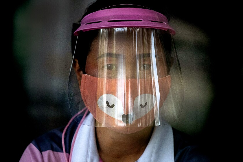 A COVID-19 screener wearing a face shield and mask.