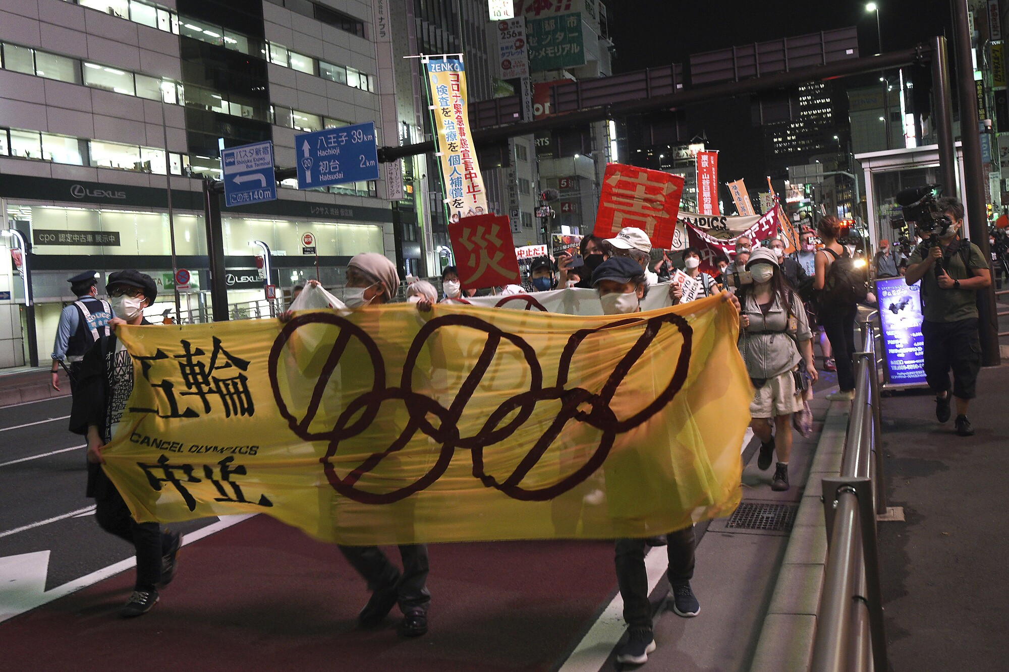 People march at night with banners and signs.