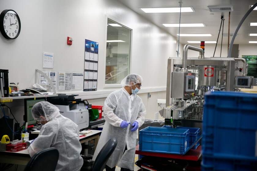 Hologic employees use a robotic filling machine to prepare specimen collection kits used to detect a wide range of infectons in this June 2019 file photo in San Diego.