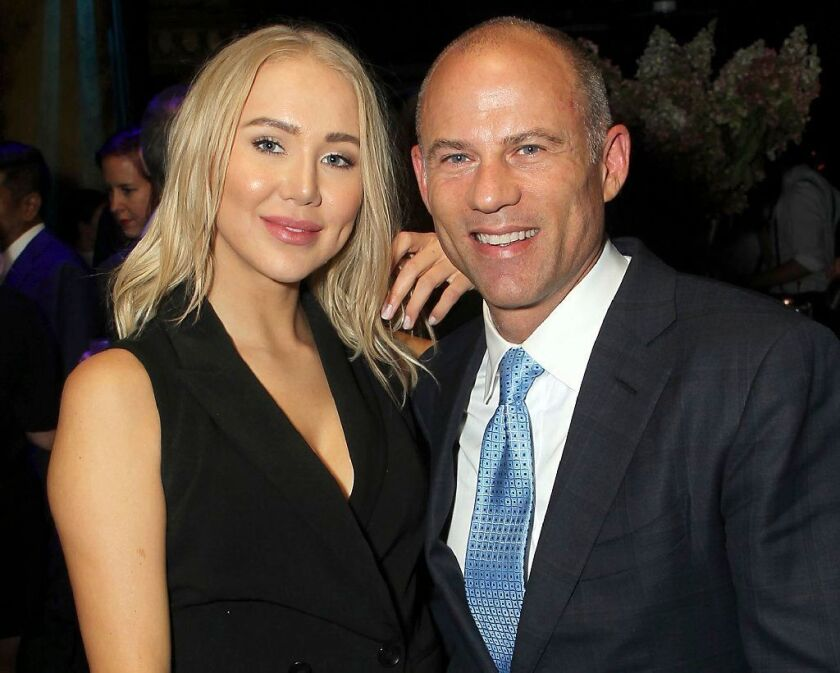 In this September 2018 photo, attorney Michael Avenatti, right, poses with Mareli Miniutti for a photo at a party in New York. Miniutti alleges that Avenatti dragged her across the floor of his Los Angeles apartment after an argument over money.