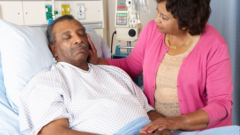 Senior woman caressing her husband in a hospital bed