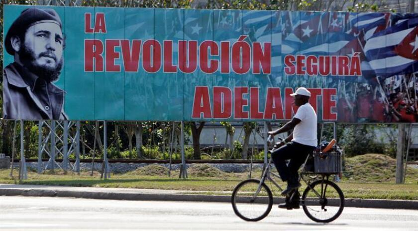 A man cycles past a sign touting the Cuban Revolution on Dec. 27, 2018, in Havana. On the sign can be seen the image of a young Fidel Castro. EFE-EPA/Ernesto Mastrascusa