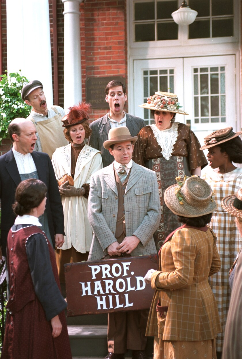 """Matthew Broderick, in costume and holding a suitcase labeled """"Prof. Harold Hill,"""" is surrounded by singing men and women."""