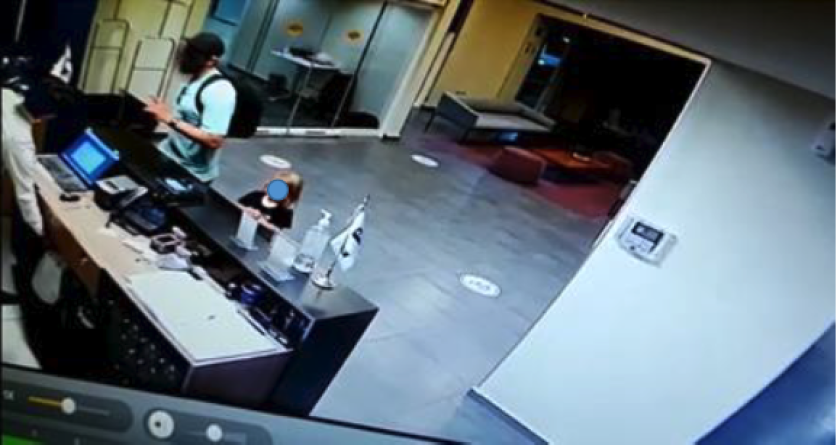 A security camera image shows a man and small child in front of a hotel desk. Both of their faces have been obscured.