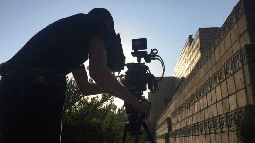 "A cameraperson works on the KCET documentary ""That Far Corner: Frank Lloyd Wright in Los Angeles"" outside the Millard House in Pasadena in 2017."