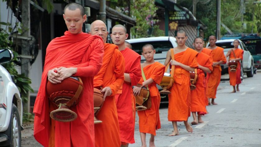 The sacred alms-giving ceremony takes place daily in the streets of Luang Prabang. CREDIT: Norma Me