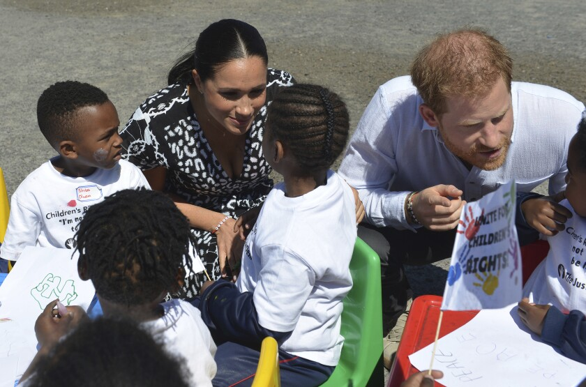 Britain's Prince Harry and Meghan Duchess of Sussex, greet children on their arrival at the Nyanga Methodist Church in Cape Town, South Africa, Monday, Sept, 23, 2019, which houses a project where kids are taught about their rights, self-awareness and safety, and are provided self-defence classes and female empowerment training to young girls in the community. The royal couple are starting their first official tour as a family with their infant son, Archie (Courtney Africa / Africa News Agency via AP, Pool)