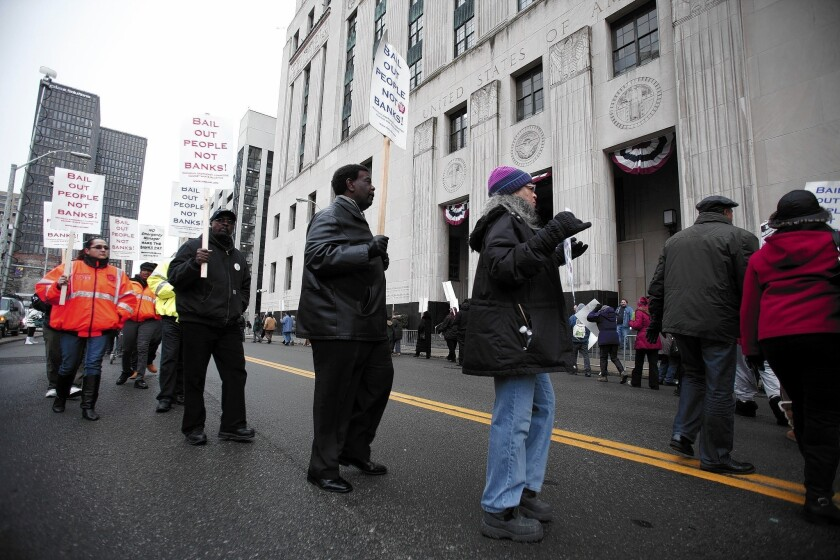 People protest outside the courthouse where U.S. Bankruptcy Judge Steven Rhodes ruled that Detroit was eligible for bankruptcy protection and that its workers' pensions could be cut.