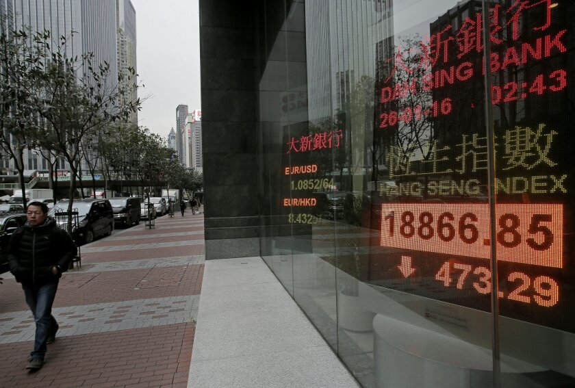 A man walks past an electronic board showing Hong Kong share index outside a local bank in Hong Kong, Tuesday, Jan. 26, 2016. Asian stock markets sank Tuesday, led by a plunge in the Shanghai index, after a renewed slump in the price of oil kept investors on edge about the global economy. (AP Photo/Vincent Yu)