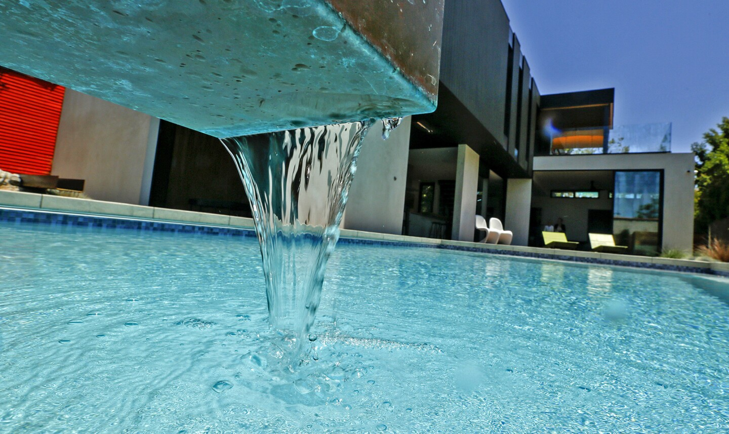 Water flows into the swimming pool through a sleek U-shaped metal channel.