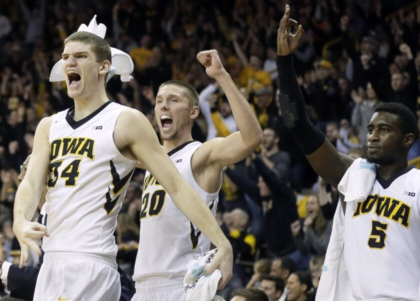 FILE - In this Jan. 24, 2016, file photo, Iowa's Adam Woodbury (34), Jarrod Uthoff (20) and Anthony Clemmons, right, react on the bench during the second half of an NCAA college basketball game against Purdue in Iowa City, Iowa. Woodbury, a senior, has been crucial for the Hawkeyes in their best se