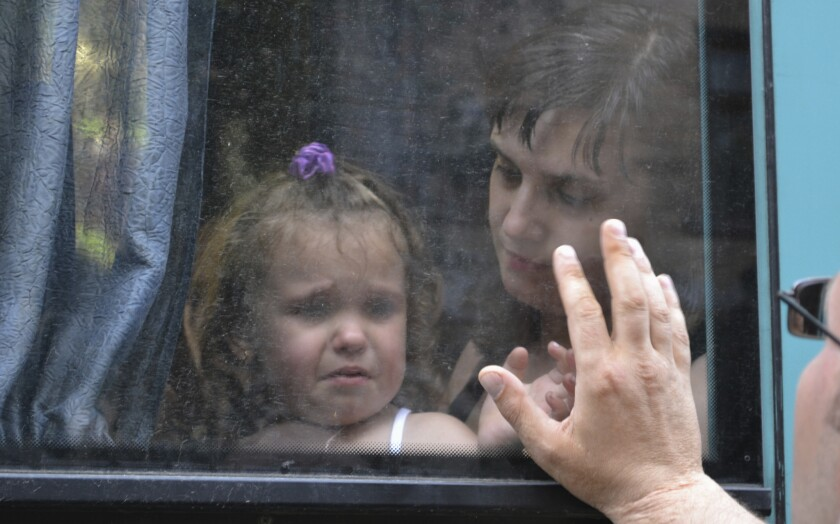 A young girl bids a tearful farewell as she waits aboard a bus to depart embattled Slovyansk in eastern Ukraine. Russia reports 30,000 have fled fighting in the area to take refuge in the Rostov region.
