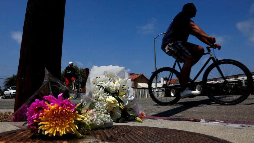 Bikers ride past a memorial left Aug. 5 for Marvin Ponce, who was shot to death at the corner of 7th and Brooks avenues.