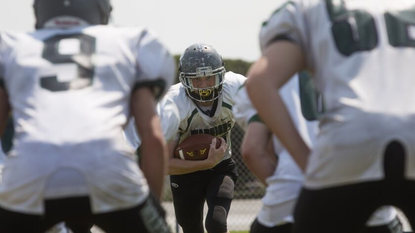 Brethren Christian's Noah Peters runs the gauntlet drill during practice in Huntington Beach on Frid
