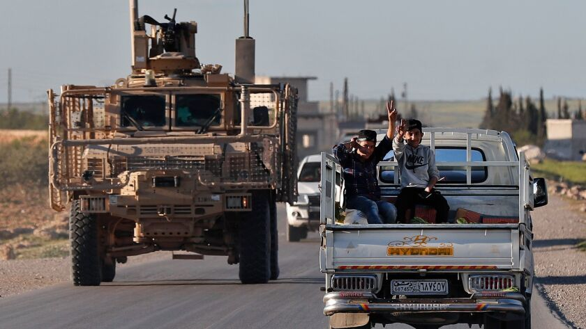 In this March 31 photo, Syrian boys travel next to a U.S. vehicle on a road leading to the tense front line with Turkish-backed fighters, in Manbij, Syria. President Trump has ordered the Pentagon to plan to withdraw U.S. troops from Syria, but held off on setting a date.