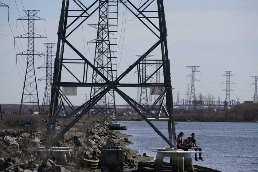 People sit at the base of a transmission tower