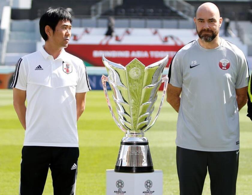 El español Félix Sánchez Blas (dcha), seleccionador de Catar, y el entrenador Moriyasu Hajime, entrenador de la selección de Japón, posan junto al trofeo este jueves en la víspera de celebración de la final de la Copa de Asia de fútbol en Abu Dabi (Emiratos Árabes Unidos). EFE