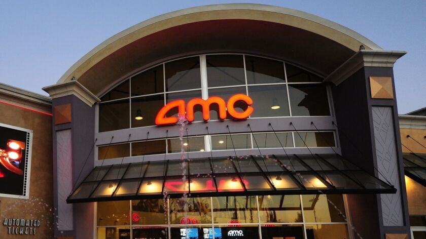A couple watch a big screen outside movie theaters of the US cinema chain AMC Entertainment in Monte