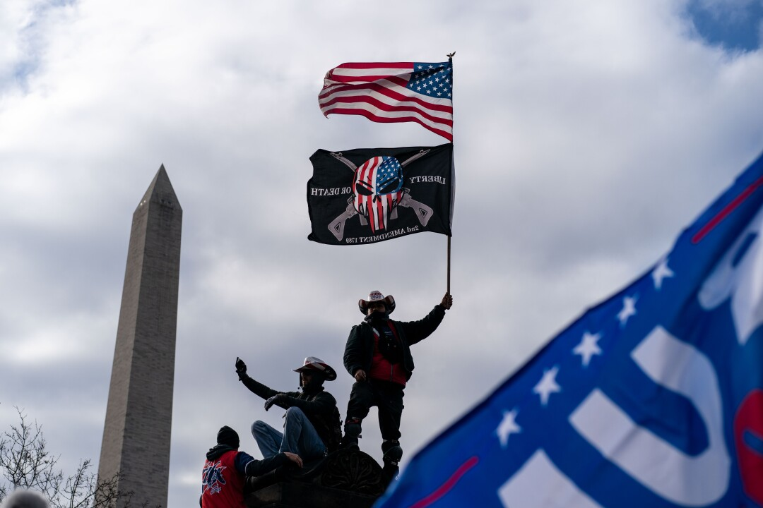 Donald Trump supporters hold flags and take a selfie with the Washington Monument in the background