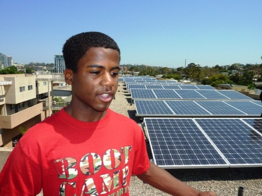 Robert Smith, 14, talks about the new solar panels installed atop the apartment complex in which he lives. The installation is the 10,000th in SDG&E's territory and the first under a program designed to help multi-family housing take advantage of solar energy.