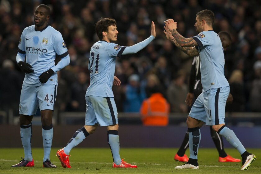 Manchester City's David Silva, centre, celebrates with teammates after scoring his first goal during the English Premier League soccer match between Manchester City and Newcastle at the Etihad Stadium, Manchester, England, Saturday Feb. 21, 2015. (AP Photo/Jon Super)