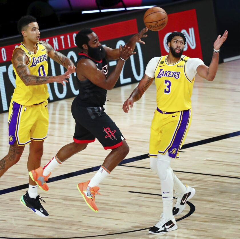 Rockets guard James Harden, center, passes the ball while defended by Lakers forwards Kyle Kuzma, left, and Anthony Davis.