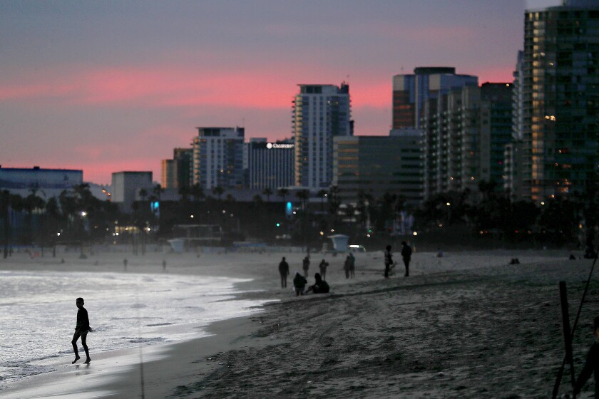 People are silhouetted at dusk on a beach with city buildings in the background.