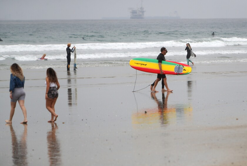 A couple of surfers leave the water at Huntington City Beach in April.