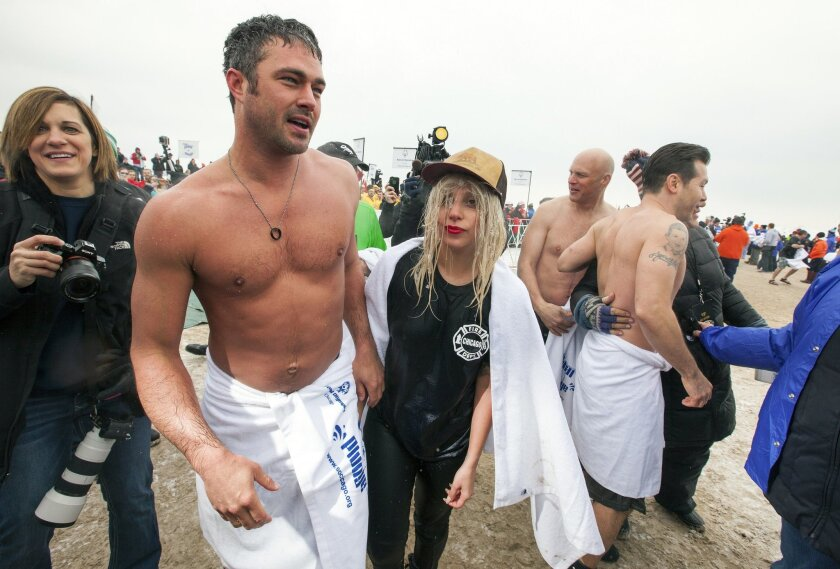 """Actor Taylor Kinney, second left, and his fiancée, pop star Lady Gaga, center, along with """"Chicago Fire"""" cast take part in the Chicago Polar Plunge at North Avenue Beach on Sunday, March 1, 2015 in Chicago. (Photo by Barry Brecheisen/Invision/AP)"""