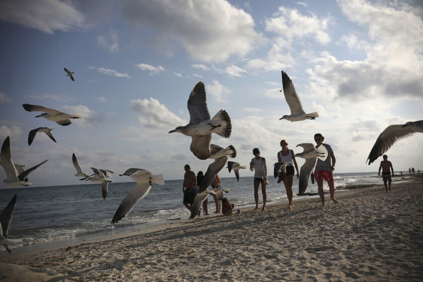 Tourists stroll on the shore of Xcalacoco beach in Playa del Carmen