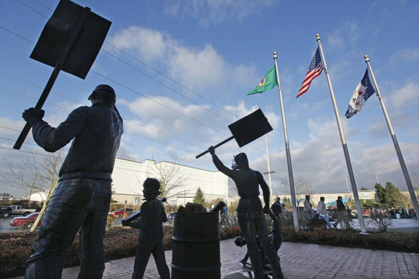 Boeing machinists walk past statues commemorating striking workers as they prepare to vote at their union hall Friday, Jan. 3, 2014, in Everett, Wash. The vote will determine Friday whether Boeing machinists will accept a contract that would concede some pension and health care benefits in order to secure assembly of the company's new 777X airplane in Washington state. (AP Photo/Elaine Thompson)