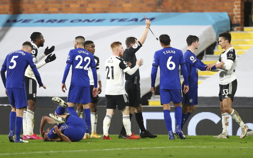 Fulham's Antonee Robinson is shown a red card by referee Peter Bankes during the English Premier League soccer match between Fulham and Chelsea at Craven Cottage in London, England, Saturday, Jan. 16, 2021. (Clive Rose/Pool via AP)