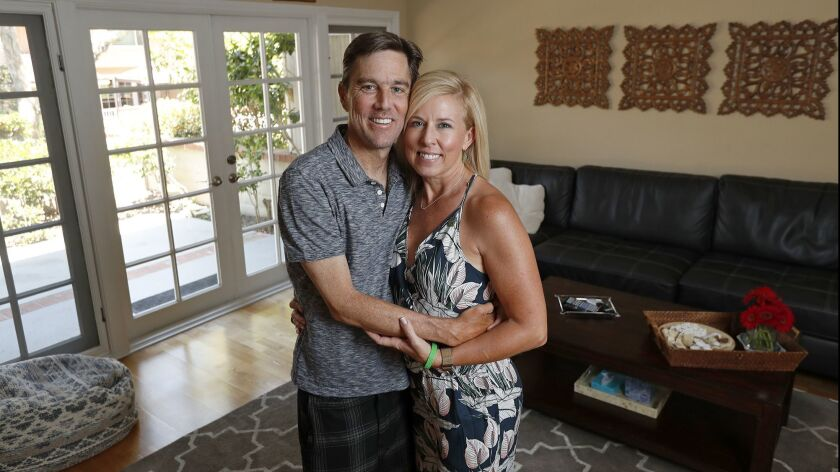 John Ward and wife Christy pose for a portrait at their home in Newport Beach on Friday, July 6. Joh