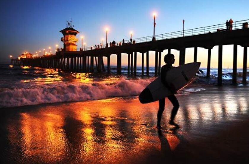 A surfer leaves the water near the Huntington Beach Pier in this file photo. The structure was closed Tuesday as the city works to contain the spread of the coronavirus.