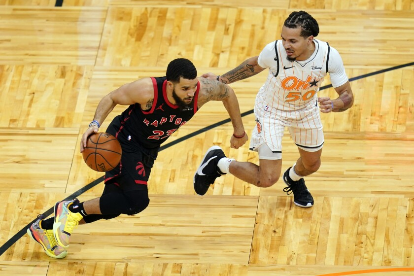 Toronto Raptors guard Fred VanVleet, left, drives around Orlando Magic guard Cole Anthony (50) during the first half of an NBA basketball game, Tuesday, Feb. 2, 2021, in Orlando, Fla. (AP Photo/John Raoux)
