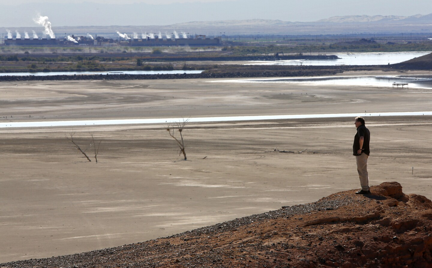 Bruce Wilcox, environmental manager with the Imperial Irrigation District, looks toward the dry lake bottom of the Salton Sea at what's known as Red Hill Marina.