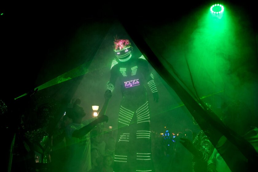 In this Feb. 12, 2016 photo, an alien enthusiast in an illuminated costume arrives for a parade at the annual Alien Festival in Capilla del Monte, Cordoba, Argentina, the site of an alleged UFO sighting 30 years ago. Thousands of earthlings gathered for the festival in this central Argentine town w