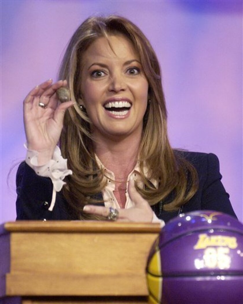 """FILE - Los Angeles Lakers Executive Vice President Jeanie Buss shows the lucky rock she was given by boyfriend Phil Jackson before the NBA Draft Lottery in this May 24, 2005 file photo taken in Secaucus, N.J. Jackson finally replaced the rock. Buss posted a picture Thursday night Jan. 3, 2013 on her official Twitter account of her left hand with a diamond ring on her finger. Buss later confirmed the engagement to ESPN.com, saying she received the ring at Christmas and she's """"beyond happy."""" (AP Photo/Bill Kostroun)"""