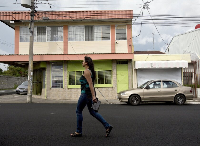 "In this July 9, 2014 photo, a woman walks in front of the building that once housed the human rights group Fundacion Operacion Gaya Internacional in Heredia, Costa Rica. Fernando Murillo was the charismatic head of the group and he'd been contracted by Creative Associates to turn Cuba's politically apathetic young people into ""change agents."" Murillo was an idealist devoted to human rights. A former boy scout, he had no experience in undercover work, yet would soon face off against one of the world's most sophisticated counter-intelligence services, on a mission for Cuba's adversary, the U.S. Before his trip to Havana on April 5, 2010, Murillo was given basic security training. (AP Photo/Esteban Felix)"