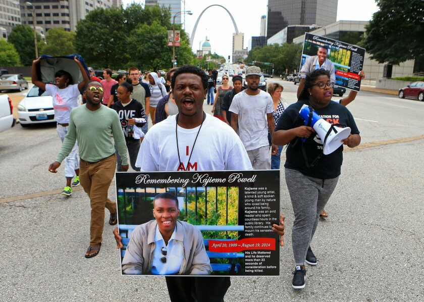 FILE - In this Aug. 19, 2015 file photo, Mike Hassell, center, leads a march to St. Louis' municipal courthouse on the one-year anniversary of the shooting death of Kajieme Powell by St. Louis police officers. St. Louis' city prosecutor says Tuesday, Nov. 3, 2015 that two police officers who fatall