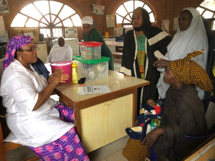 Nutritionist Salamatu Jibril, left, talks to a woman, seated at right, who runs an orphanage in Kaduna, Nigeria. The woman had rushed a 1-month-old weighing under 6 pounds to Barau Dikko Teaching Hospital.