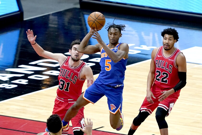 New York Knicks' Immanuel Quickley (5) looks to pass between the defense of Chicago Bulls' Tomas Satoransky (31) and Otto Porter Jr. during the first half of an NBA basketball game Monday, Feb. 1, 2021, in Chicago. (AP Photo/Charles Rex Arbogast)