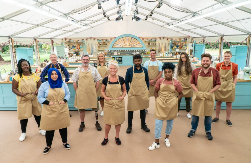Twelve cast members of 'The Great British Baking Show,' all in tan aprons, stand in a large kitchen tent.