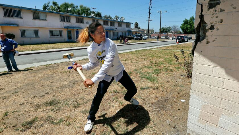 A 17-year-old resident of the Jordan Downs Housing Development in Watts takes a swing at a building that will eventually be knocked down, during a groundbreaking ceremony on Aug. 12.